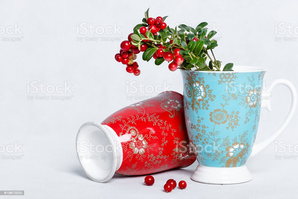 ripe lingonberries and varicolored cups with ornament stock photo