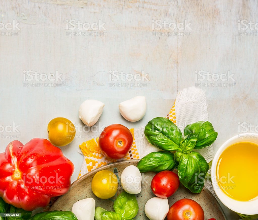 ripe multicolor tomatoes, mozzarella balls with basil leaves stock photo