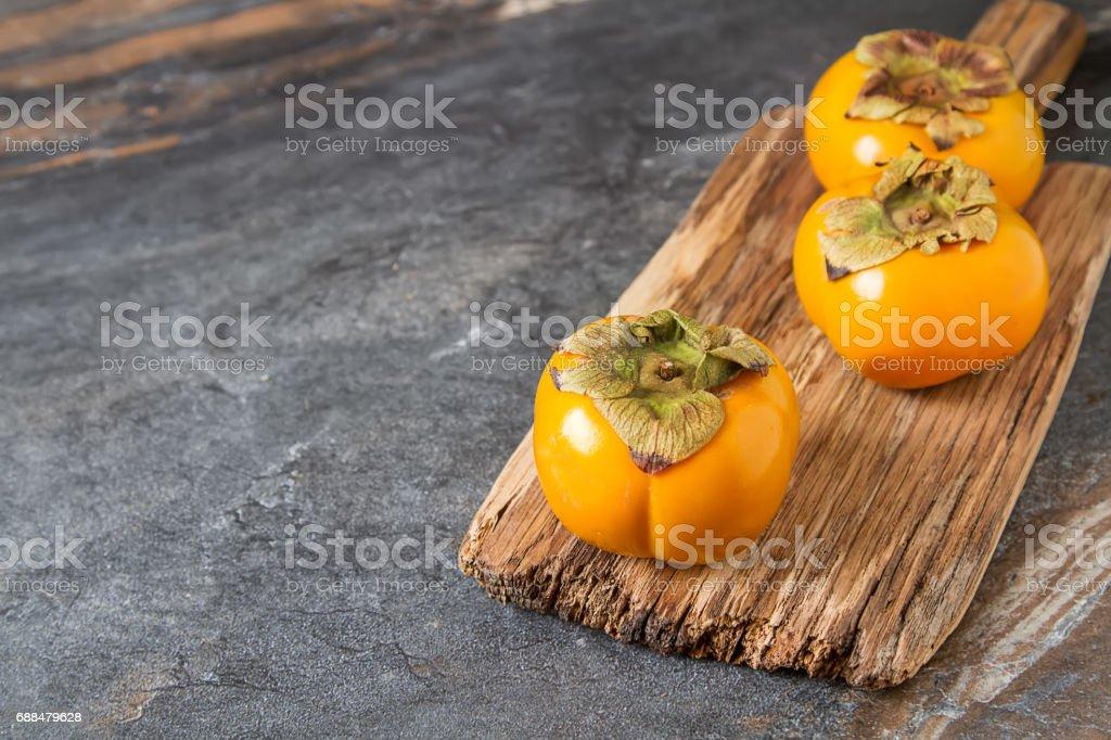 Ripe orange persimmon. Diet, or the concept of vegetarian food. Dark background. stock photo