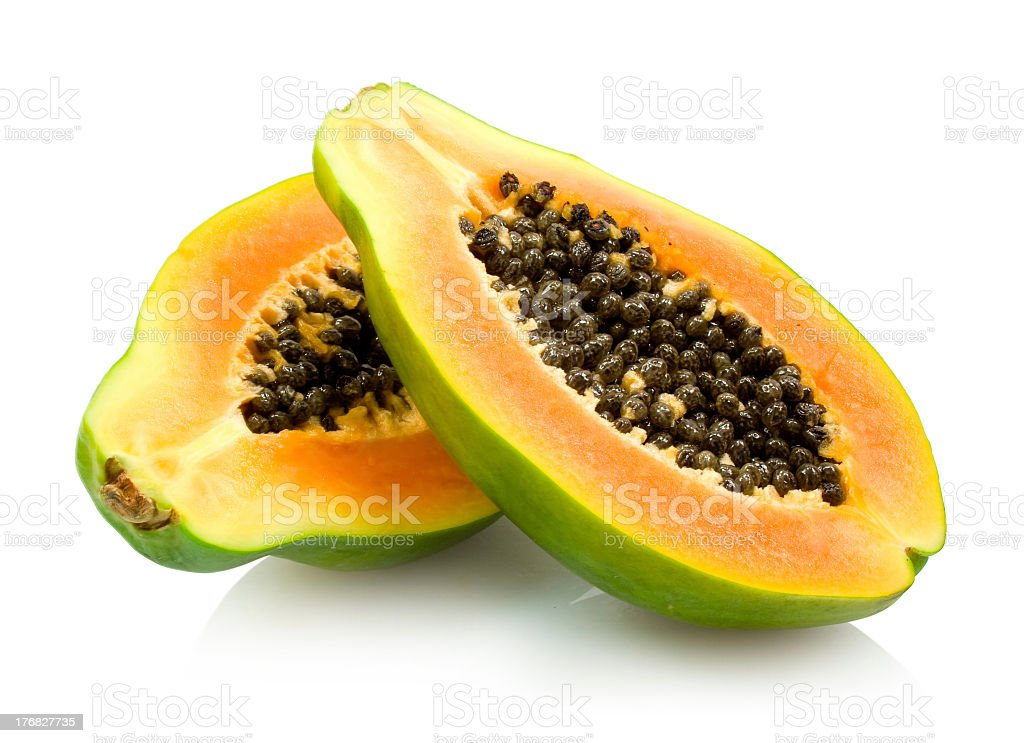 A ripe papaya cut in half showing seeds on white background stock photo