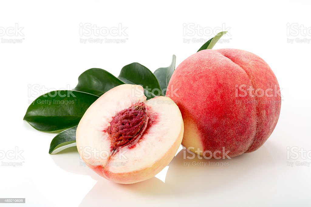 Ripe peach fruits with green leaves isolated on white background stock photo
