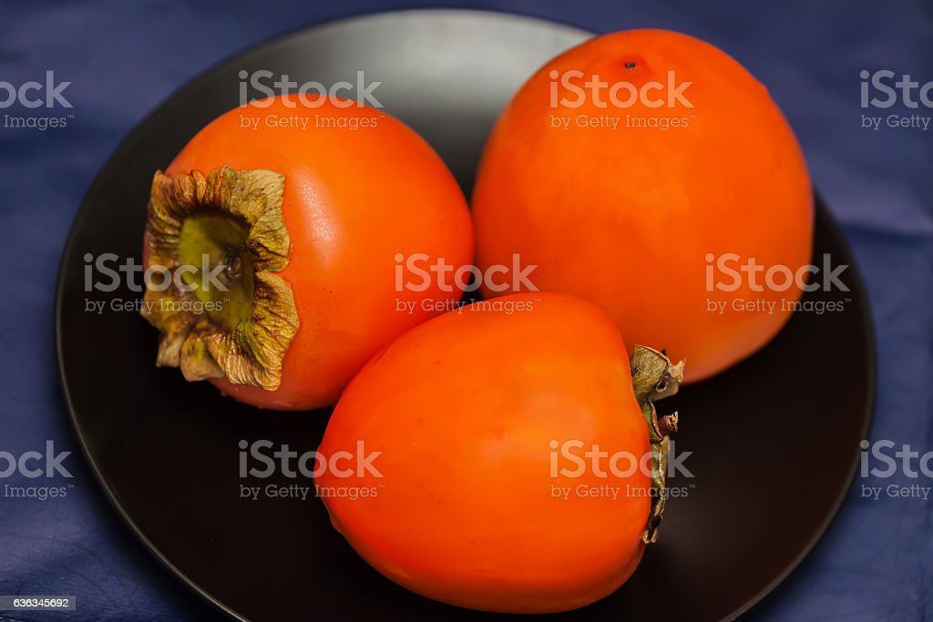 Ripe persimmon fruits in black plate, low key.This ruit stock photo