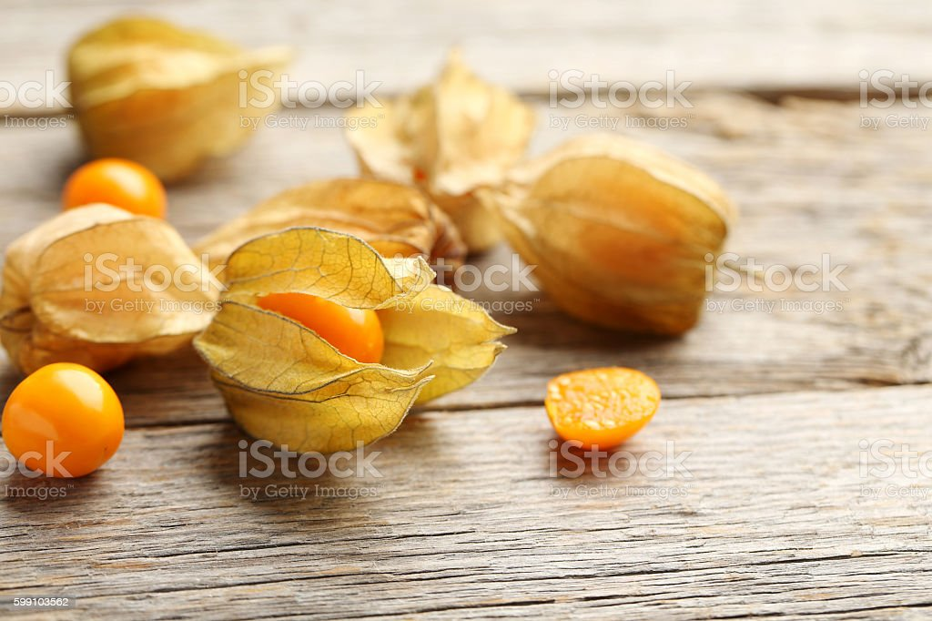 Ripe physalis on a grey wooden table stock photo