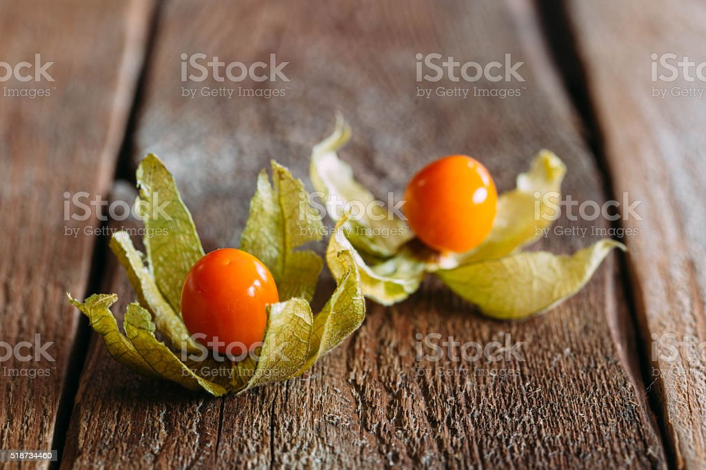 ripe physalis on wooden background stock photo