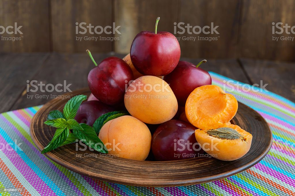Ripe plums (variety: 'Greengage') and apricots in a clay bowl stock photo