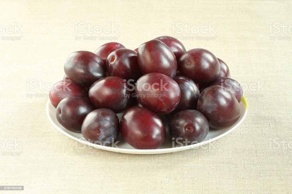 Ripe purple plums on white plate on linen cloth. Closeup stock photo