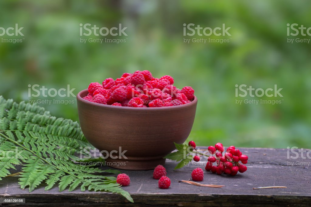 ripe raspberries in a bowl on old wooden table with a blurred background stock photo
