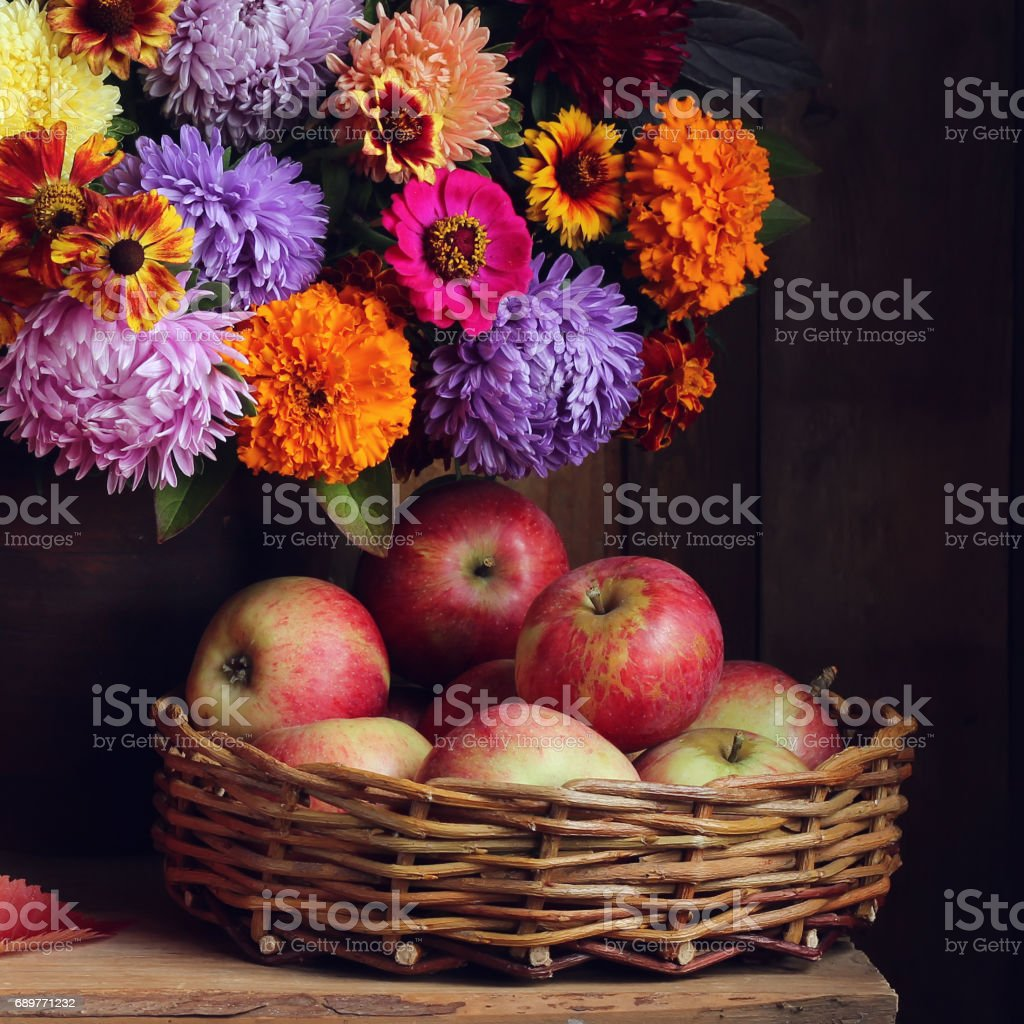 Ripe red apples in a basket and autumn bouquet. stock photo