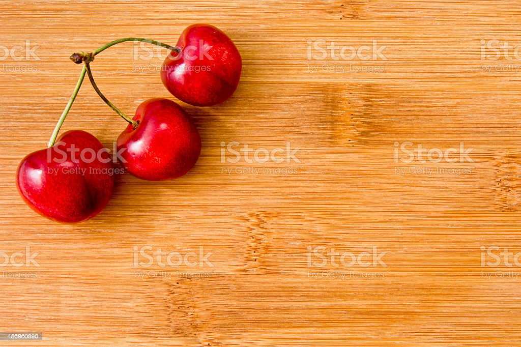 Ripe red fruit cherries on board stock photo