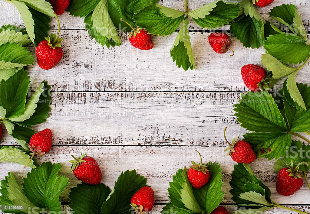 Ripe strawberries and leaves on a light wooden background. stock photo