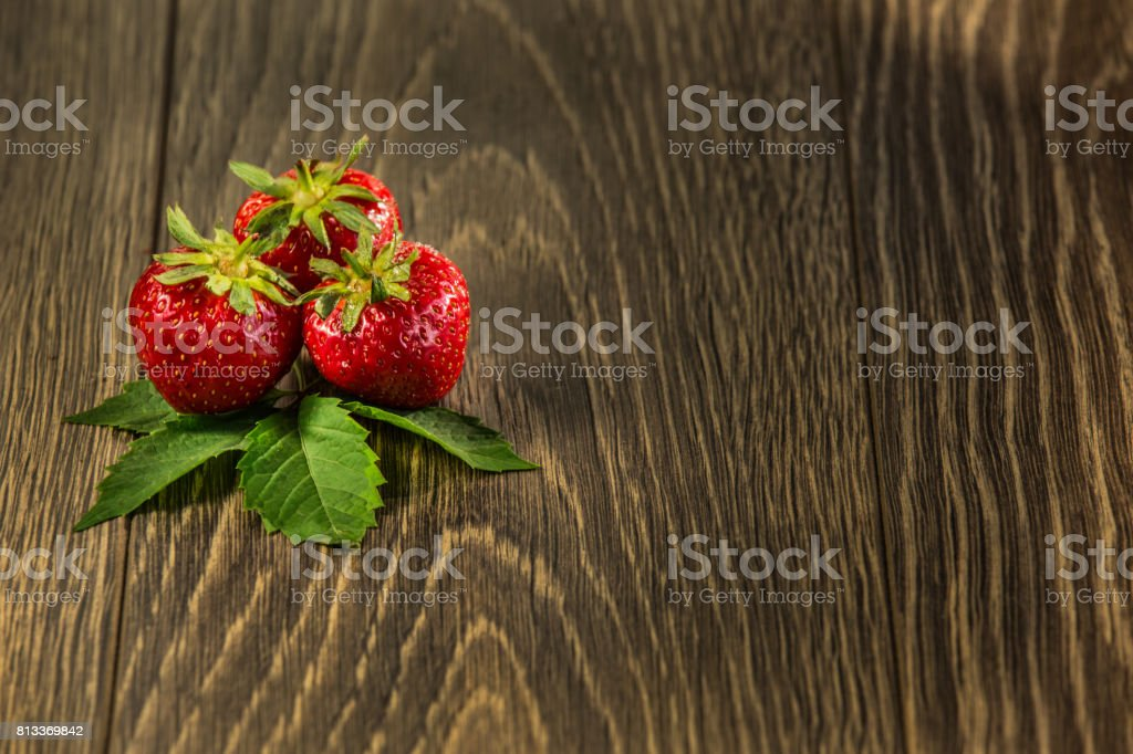 Ripe strawberries on wooden table. Fresh strawberries on wooden background. Strawberries on old wood table - background. stock photo