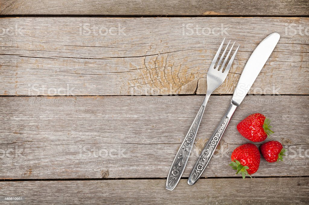 Ripe strawberries with silverware over wooden table background stock photo