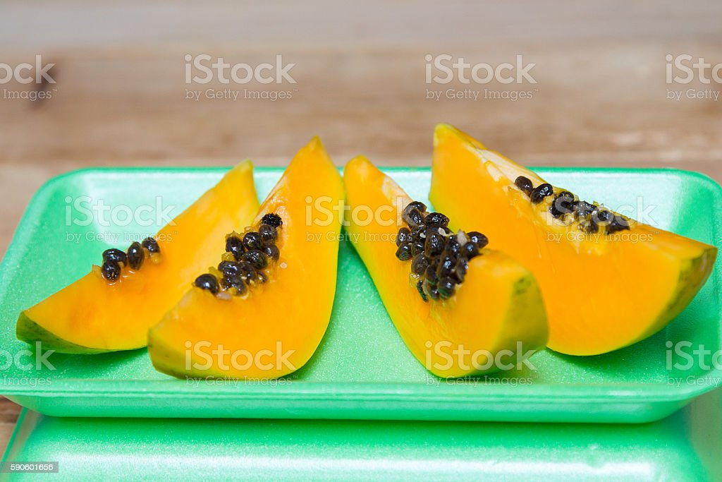 Ripe sweet papaya on green background stock photo