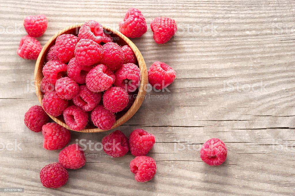 Ripe sweet raspberries in bowl on wooden table. stock photo