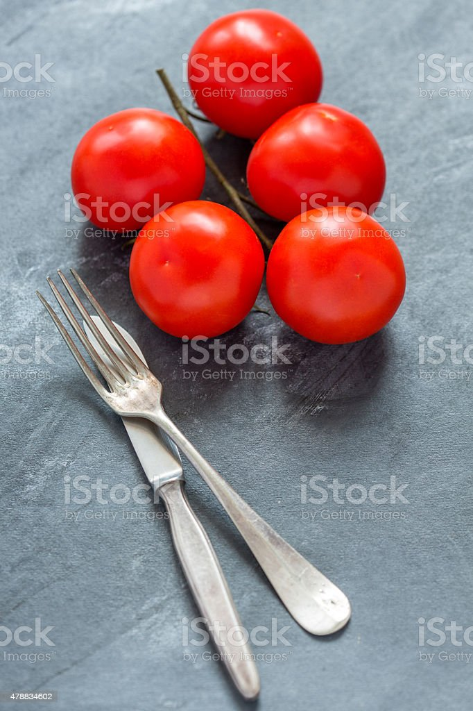 Ripe tomatoes and cutlery. stock photo