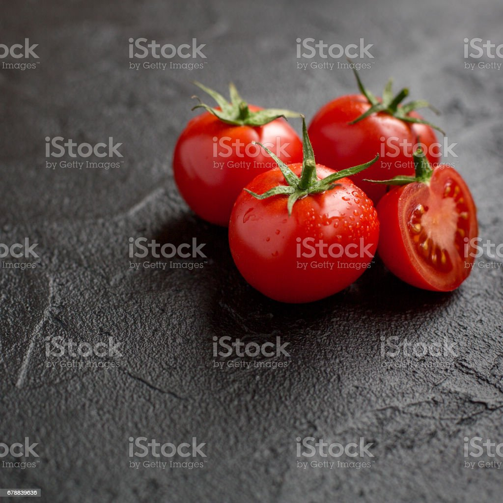 ripe tomatoes on black marble stock photo