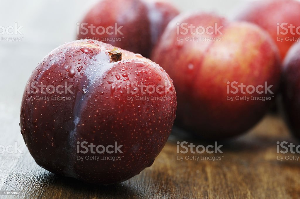 ripe wet plums on oak surface royalty-free stock photo