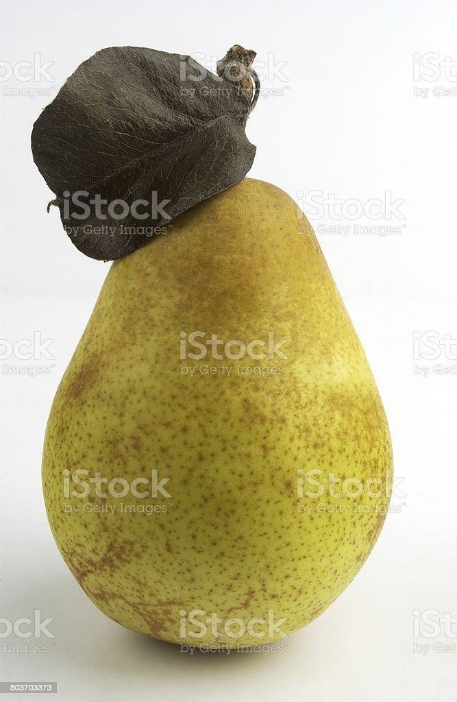 Ripe yellow pear with a dead leaf on a white background stock photo