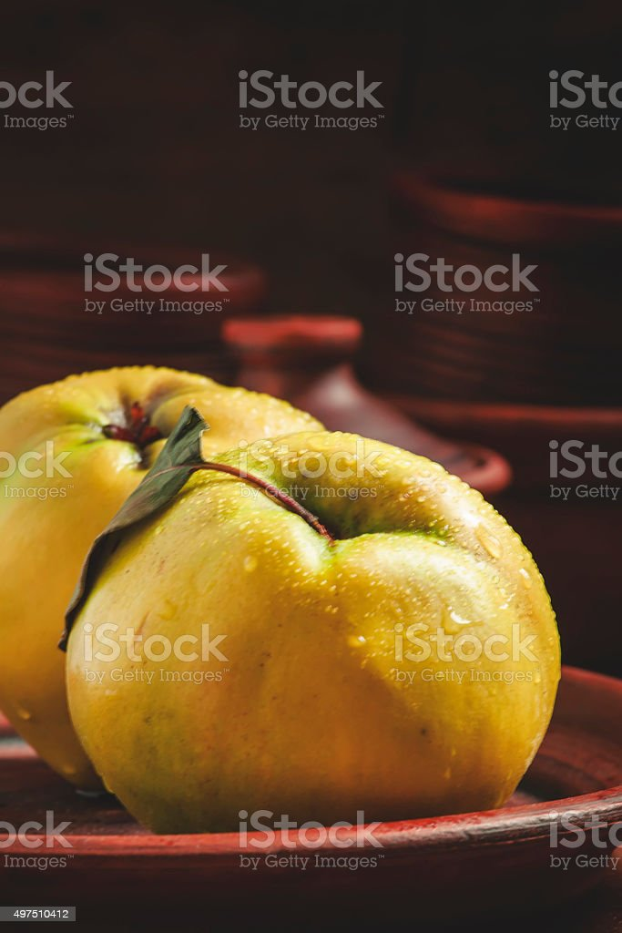 Ripe yellow quince on a clay plate stock photo