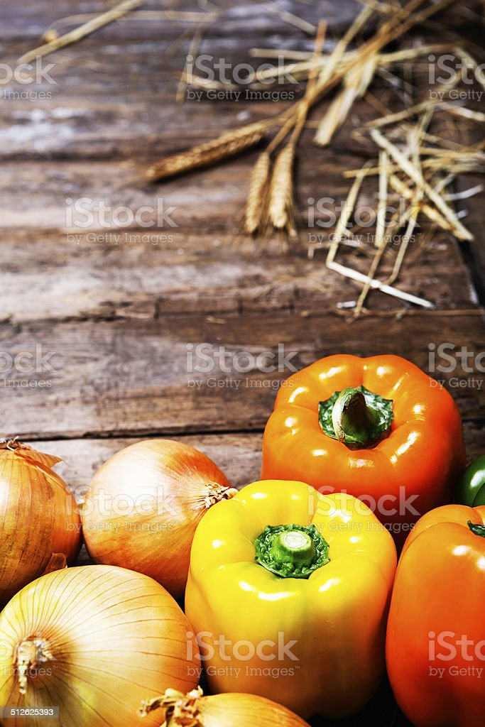 Ripe yellow sweet peppers and other vegetables on wood stock photo