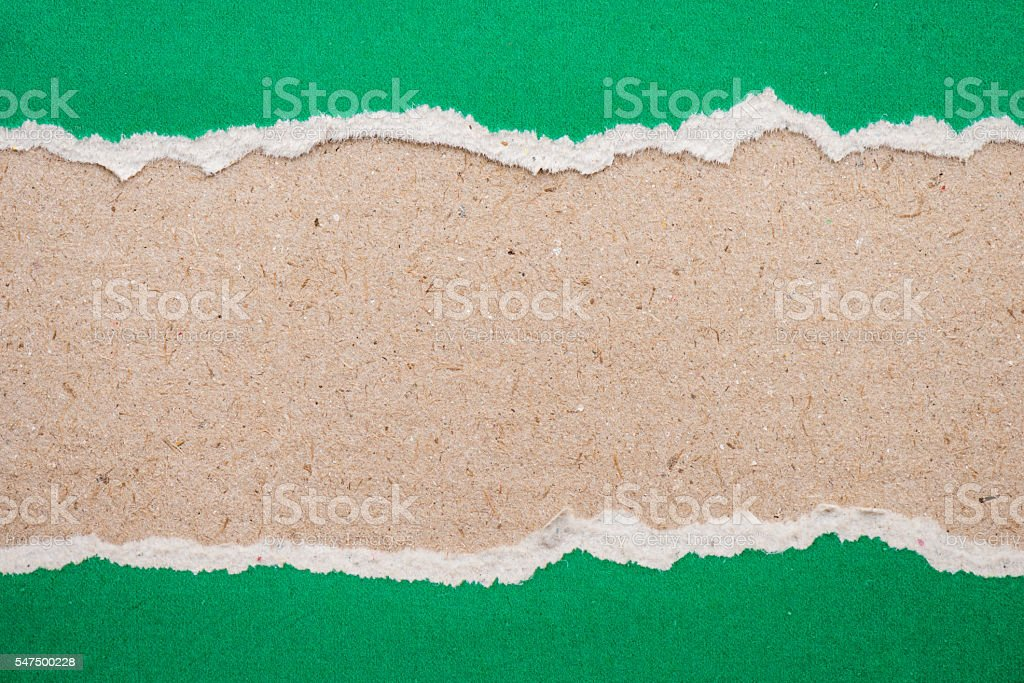 ripped green paper on brown background stock photo