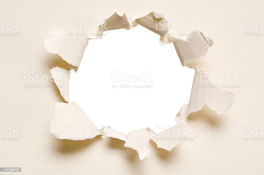 Ripped hole in a paper, isolated stock photo