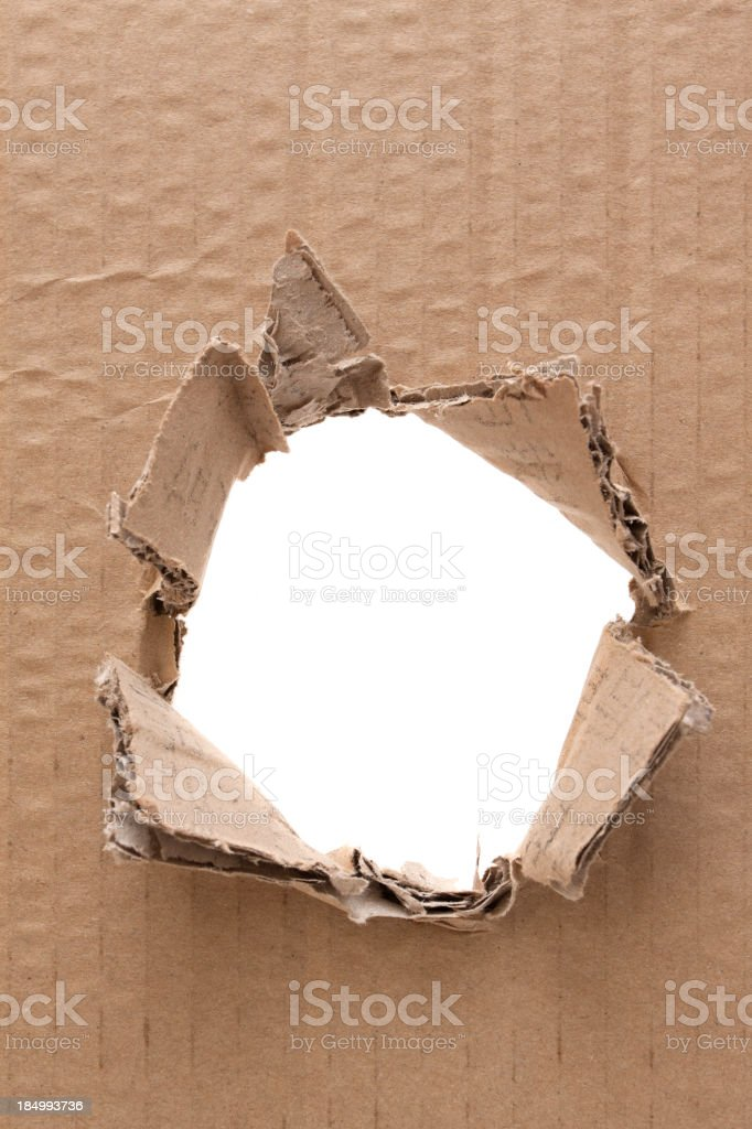 Ripped hole in cardboard background textured stock photo