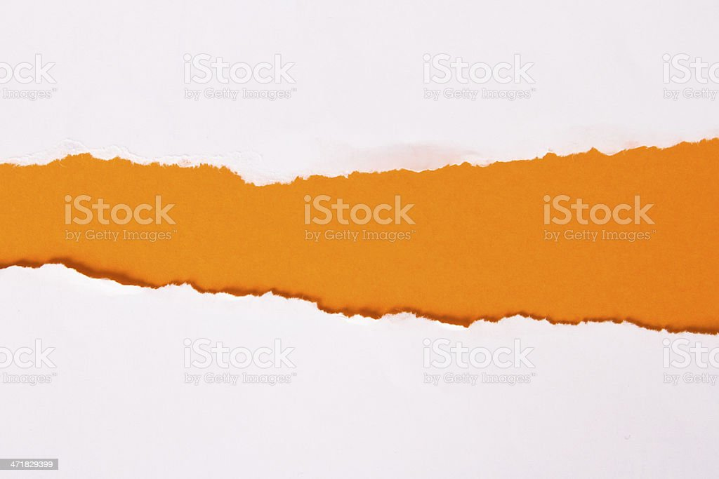 Ripped white paper revealing orange-colored background stock photo