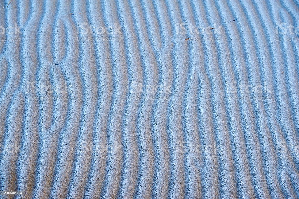Rippled frosty sand on beach stock photo