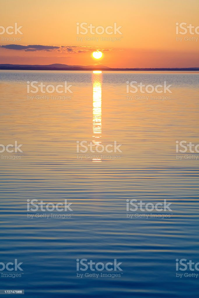 Ripples on the water in front of the orange sun setting royalty-free stock photo