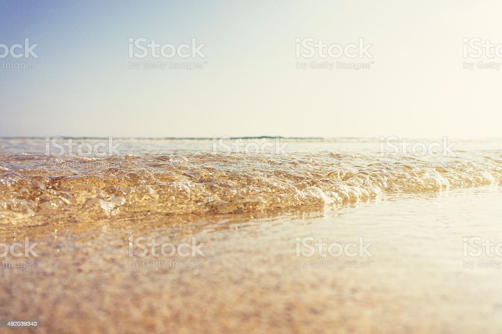 rippling shallow wave rolling onto a warm beach stock photo