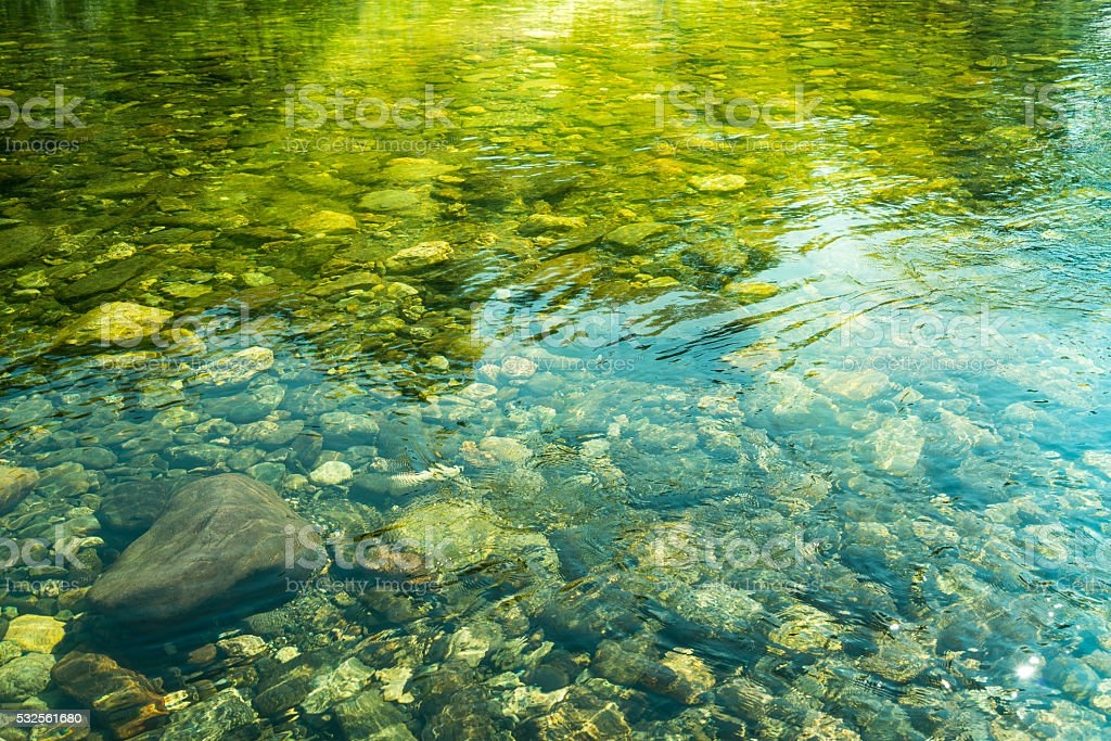 Rippling water with sunbeam and stones in the water stock photo