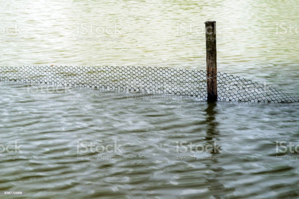 Rippling Waters with Wooden Fence Post stock photo