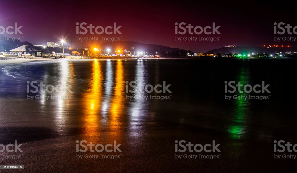 Rishikonda Beach at night with city lights and hills stock photo
