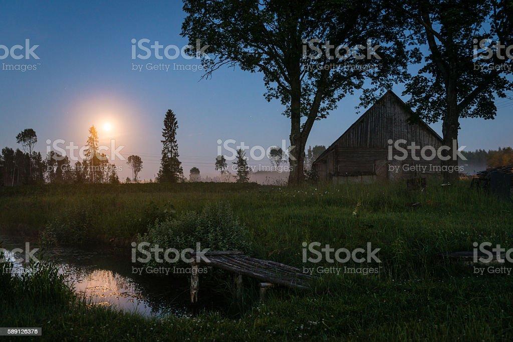 Rising moon over a foggy Latvian countryside at dusk stock photo