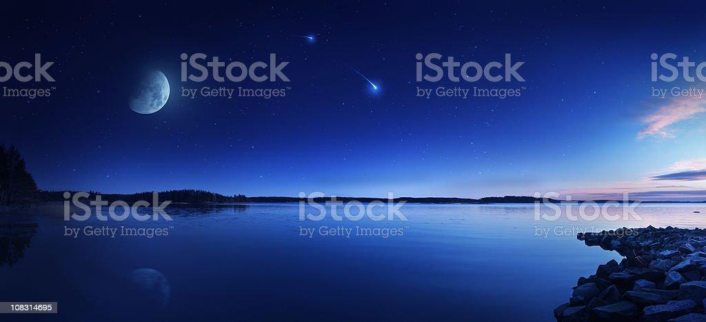 Rising moon over lake stock photo