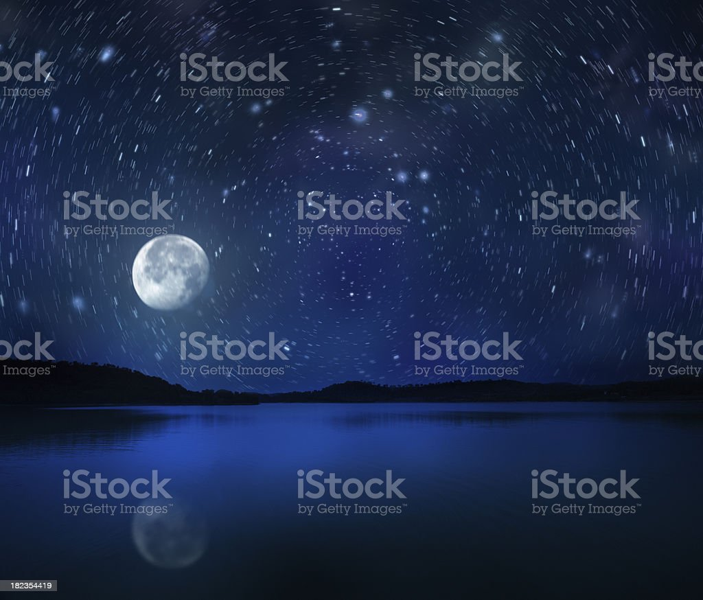 Rising moon over lake royalty-free stock photo