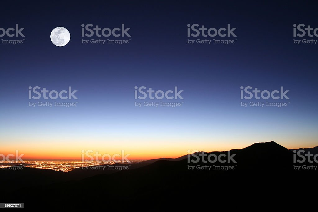 rising moon over mountains stock photo