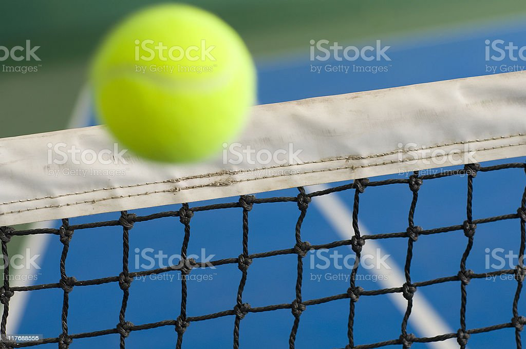 Rising tennis ball in action over the net stock photo