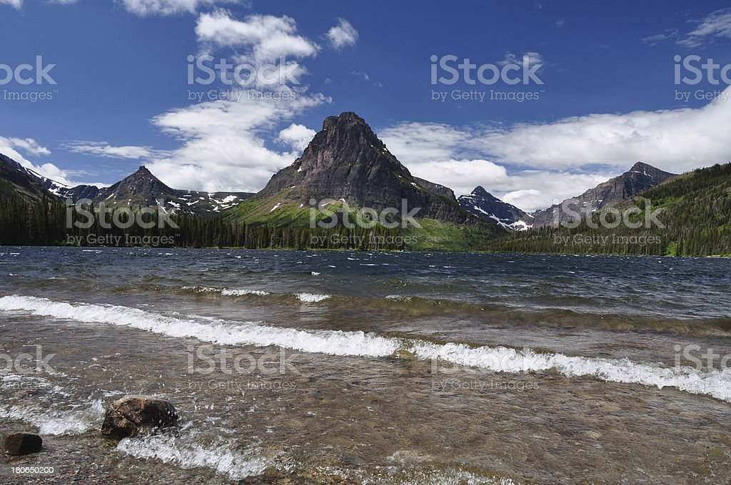 Rising Wolf Mountain rises behind waves of Two Medicine Lake royalty-free stock photo