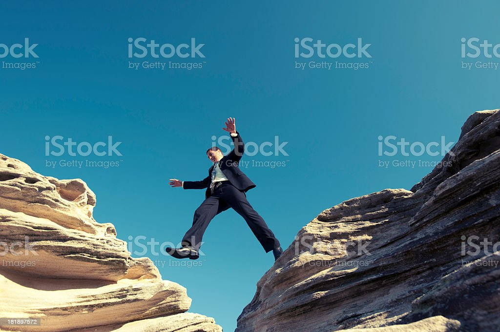 Risk concept. Businessman jumping across a ravine. stock photo