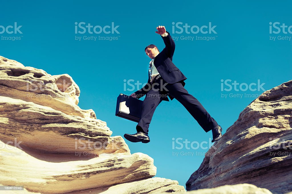 Risk concept. Businessman jumping across a ravine with briefcase stock photo