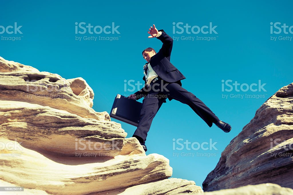 Risk concept. Businessman jumping across a ravine with briefcase royalty-free stock photo