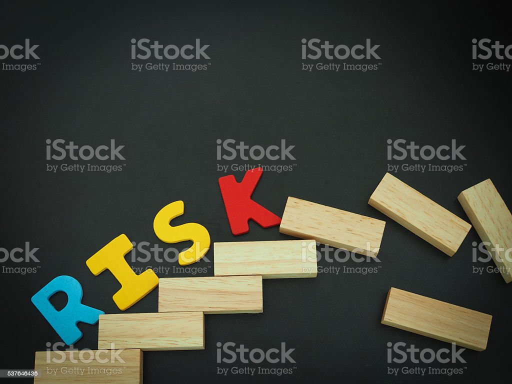 Risk. Wood stacking step stair with 'RISK' word black background stock photo