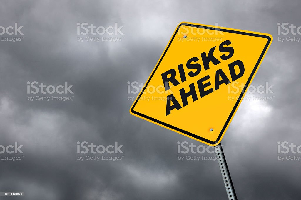 Risks ahead road sign in front of cloudy sky background royalty-free stock photo