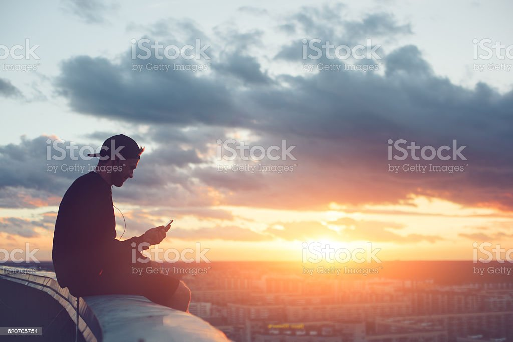 Risky man with smartphone chilling on the roof stock photo