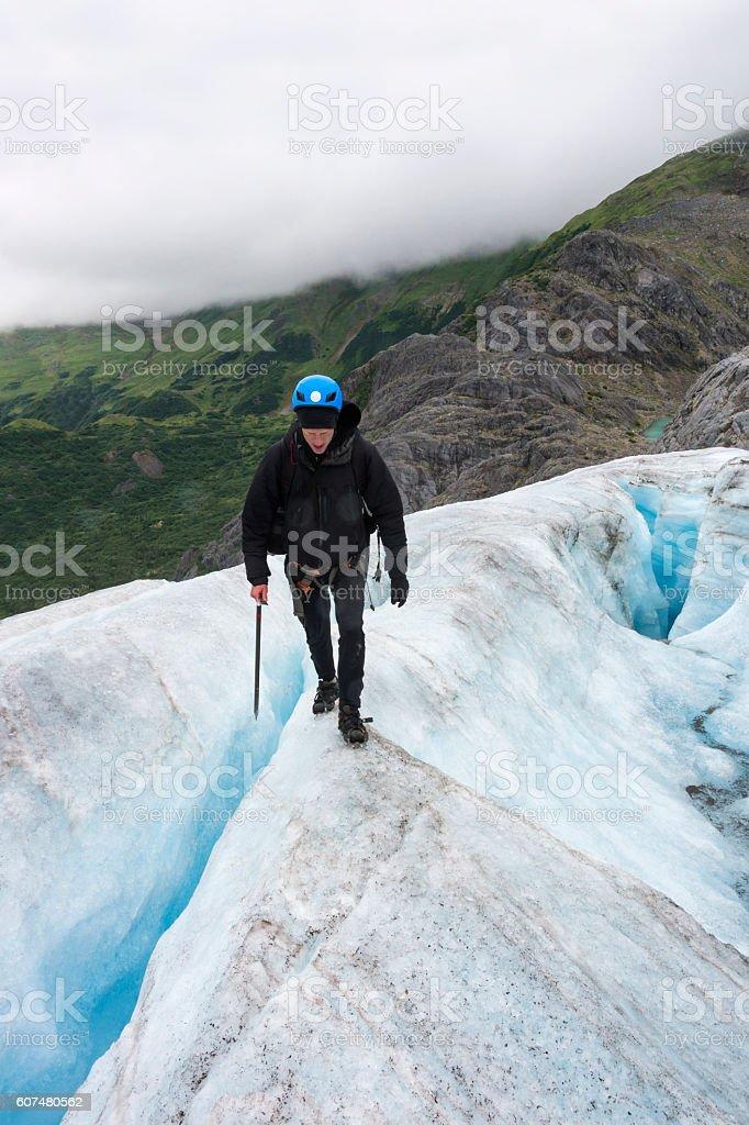 Risky walk between crevasses on icy glacier stock photo
