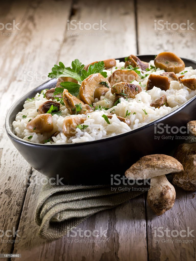 Risotto with cep mushrooms served on plate on wood surface stock photo