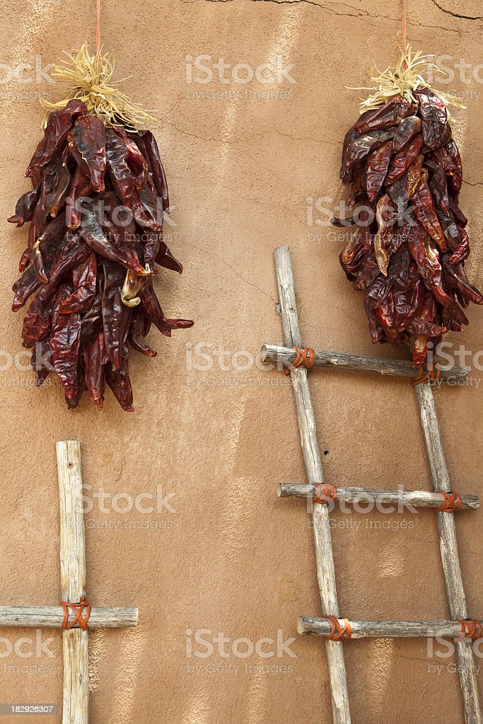 Ristras of Chili Peppers Hang on Adobe Wall stock photo