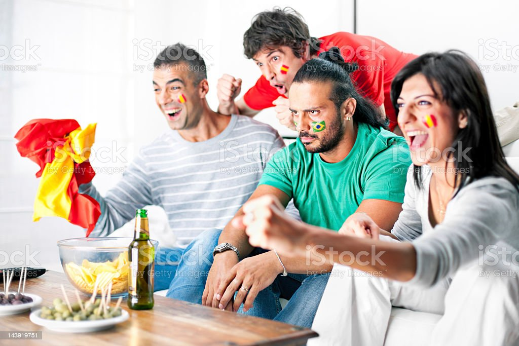 Rival soccer team fans cheering in living room royalty-free stock photo
